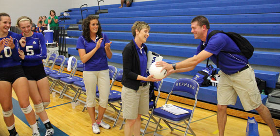 Assistant Coach Phil Landolt hands Head Coach Linda Lampkin the game ball after winning her 800th career win.